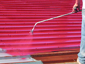 Red paint is used to coat a rusty rooftop