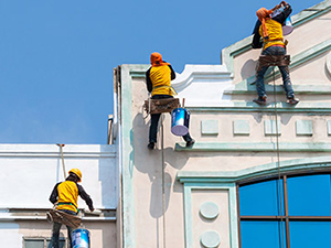 Workers apply protective paint on the outside walls of a building