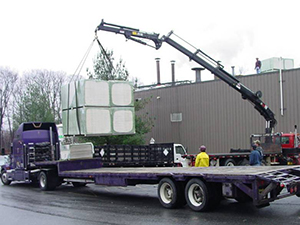 A crane lifts roofing supplies of a trailer at a commercial facility