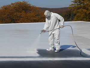Worker sprays white coating on commercial roof