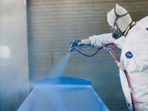 Man sprays blue paint on metal